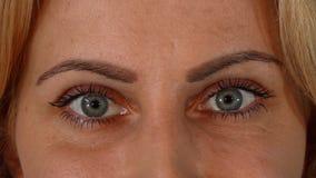 Bei occhi azzurri di una donna matura che guarda alla macchina fotografica video d archivio