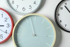 Bei orologi differenti che appendono sulla parete leggera fotografia stock libera da diritti