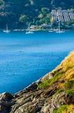 Bei paesaggio e tropicale sopra il mare ed il capo blu con la barca a vela nella priorità alta del capo della roccia e del fondo Fotografie Stock