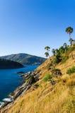 Bei paesaggio e tropicale sopra il mare ed il capo con il mare blu, il fondo del cielo e la priorità alta gialla dell'erba Fotografia Stock