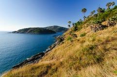Bei paesaggio e tropicale sopra il mare ed il capo con il mare blu, il fondo del cielo e la priorità alta gialla dell'erba Fotografia Stock Libera da Diritti