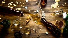 Bei Partei - verschüttetes Bier, Flaschenkapseln und übrig gebliebene Chips auf dem Tisch Lizenzfreie Stockbilder