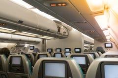 Bei passeggeri aspettanti di servizio dell'addetto dell'assistente di volo o di lotta a bordo in aerei interni fotografia stock libera da diritti