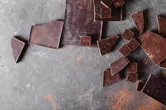 Bei pezzi e cacao in polvere del cioccolato Pezzi di Antivari di cioccolato Una grande barra di cioccolato su fondo astratto grig fotografie stock libere da diritti