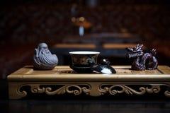 Bei piatti per un primo piano di cerimonia di tè su un bordo di legno con le statue fotografia stock