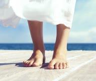 Bei piedi di una donna in vestito bianco su un pilastro di legno Sea Fotografia Stock Libera da Diritti