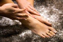 Bei piedi e mani della donna che toccano la pelle molle, viziando cura della mano e del piede, manicure francese di lusso e pedic immagini stock libere da diritti
