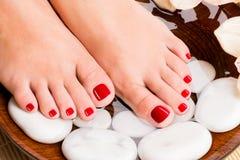 Bei piedi femminili con il pedicure rosso Fotografie Stock Libere da Diritti