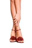 Bei piedi femminili in pattini rossi su una parte posteriore di bianco Fotografia Stock Libera da Diritti