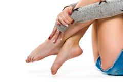 Bei piedini femminili su una priorità bassa bianca Immagini Stock