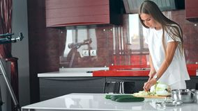 Bei prodotti di taglio della giovane donna in cucina stock footage