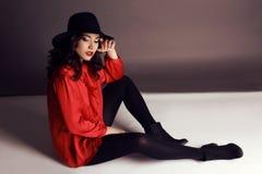 Bei ragazza con capelli scuri in blusa rossa elegante e black hat immagine stock