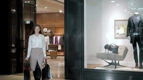 Bei sacchetti della spesa di trasporto della donna di affari mentre camminando lungo il centro commerciale in vestito di lusso stock footage