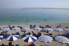 Bei sedie di spiaggia degli amanti del sole della spiaggia di Monterosso e parasoli, Cinque Terre immagine stock