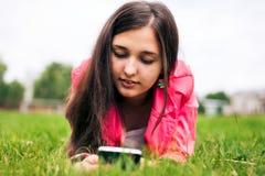 Bei sms di scrittura della ragazza sul vostro smartphone Fotografie Stock