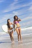 Bei surfisti & surf delle donne del bikini alla spiaggia Immagine Stock