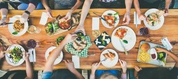 Bei Tisch essen und Freizeitkonzept - Gruppe von Personen, die mit Lebensmittel zu Abend isst lizenzfreie stockfotografie