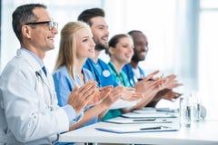 Bei Tisch sitzende und klatschende Doktoren Lizenzfreies Stockbild