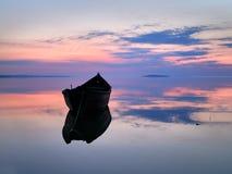 Bei tramonto/alba sopra acqua ed il peschereccio della siluetta Immagini Stock