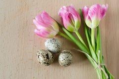 Bei tulipani con le uova di quaglia su fondo di legno leggero fotografie stock