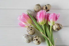 Bei tulipani con le uova di quaglia su fondo di legno leggero Fotografie Stock Libere da Diritti