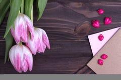 Bei tulipani rosa con su fondo di legno con le buste e la Purple Heart al valor militare Copi lo spazio Rosa rossa nozze Fotografie Stock
