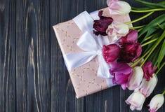 Bei tulipani viola rosa variopinti e contenitore di regalo sulla tavola di legno grigia Biglietti di S. Valentino, fondo della mo fotografia stock libera da diritti