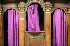 Beichtstuhl mit purpurroten Trennvorhängen Stockfotos