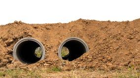Beide Betonrohre werden im Boden begraben Lizenzfreie Stockfotos