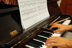 Beide handen op pianotoetsenbord met muziek noteren Stock Afbeelding