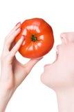 Beißende Tomate der jungen Frau Stockbilder