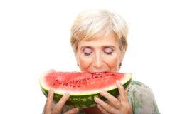 Beißende Wassermelone der älteren Frau Lizenzfreie Stockfotografie