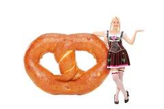 Beiers meisje die op een enorme pretzel leunen stock foto