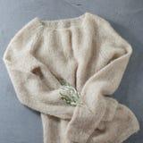 Beiga stucken woolen tröja på en hängare Fotografering för Bildbyråer