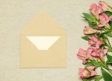 Beige ambachtenvelop met document en bloemen op steenachtergrond stock afbeeldingen