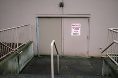 Emergency backdoor of the business. Beige backdoor of a business with `Fire exit, please keep clear` sign on it royalty free stock images