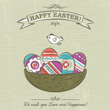 Beige background with nest full of easter eggs Stock Photos