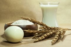 On a beige background, the products are for baking. Flour, egg, wheat ears, milk royalty free stock image