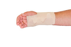 Beige bandage for his wrist. Injured male hand wrapped with Beige bandage for the wrist, isolated against white background stock photography