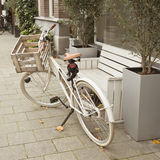 Beige bicycle parked near bench Stock Photography