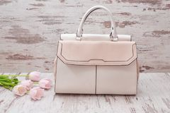 Beige big bag on a wooden background, pink tulips. Fashionable concept Stock Photography