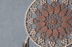 Beige broun crochet doily dream catcher. Close up on gray textured background. Copy space for text stock photo
