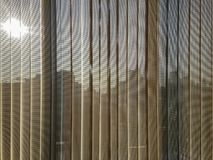 Beige vertical blinds with city background. Beige, brown color semi transparent vertical blinds with blurred afternoon sun and business district buildings seen Stock Images