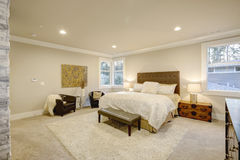 Beige and brown master bedroom boasts tufted queen bed Stock Photo