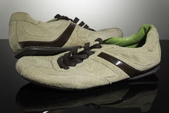 Beige/brown sneakers at glossy black surface Royalty Free Stock Image