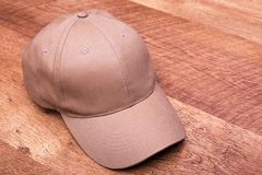 Beige cap on laminate. Men`s cap is flesh-colored. The rescuer from the sun stock photos