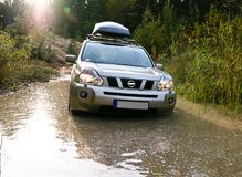 Beige car got stuck in a huge pit full of dirty water Royalty Free Stock Photography