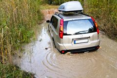 Beige car got stuck in a huge pit full of dirty water. On a forest road, hole, dirty, messy Stock Images