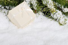 Beige christmas present in snow Stock Image