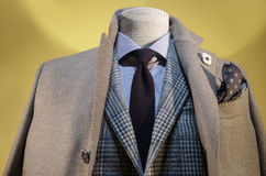 Beige Coat & Checkered Jacket. Close up of a mannequin in beige coat, checkered Jacket, striped shirt and dark blue tie stock photography